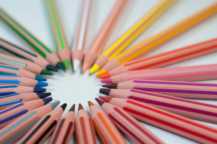 Variety of colored pencils layed flat in a circular pattern